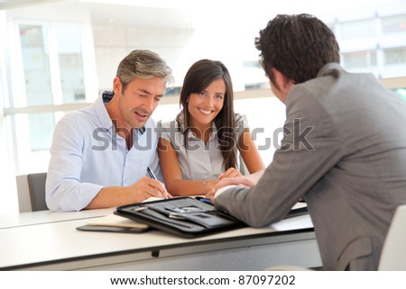 Father and teenager signing loan contract - stock photo