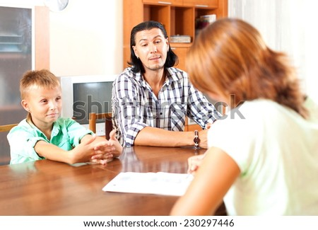 Father and teenager son talking with employee in home