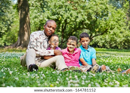 Father and three sons sit on ground in summer park - stock photo