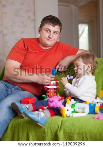 father and  three-year child plays with meccano set in home interior - stock photo