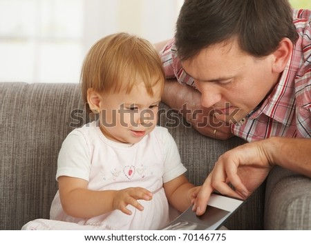 Father and toddler looking at book on sofa at home.? - stock photo