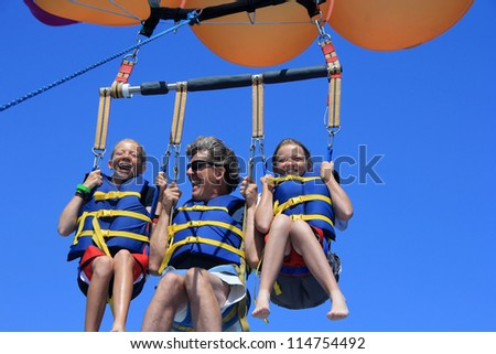Father and Twin Daughters Parasailing Against a Blue Summer Sky. - stock photo
