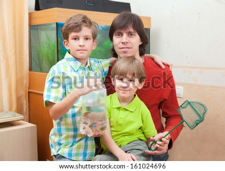 Father and two boys with tropical fish against aquarium - stock photo