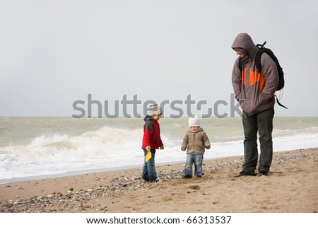 father and two children on beach - stock photo