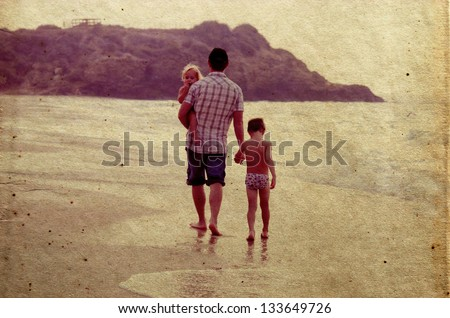 Father and two kids silhouettes on the beach at sunset - stock photo
