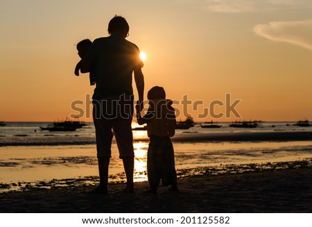 Father and two kids silhouettes on the beach at sunset, family concept - stock photo