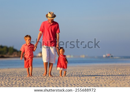 father and two kids walking on summer sand beach