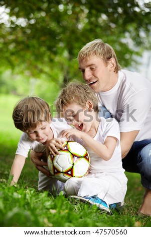 Father and two sons play football in a summer garden - stock photo