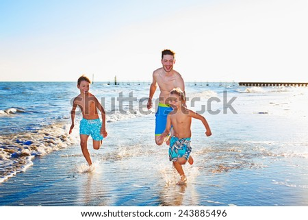 Father and Two Sons Running at the Beach While Playing on a Tropical Climate. - stock photo