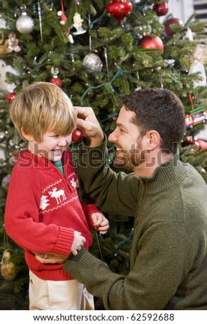 Father and 4 year old son playing in front of Christmas tree