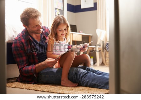 Father and young daughter reading together - stock photo