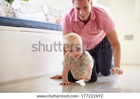 Father And Young Son Crawling Around Room Together - stock photo