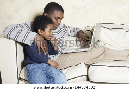 Father and young son with laptop on sofa