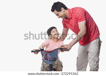 Father assisting son in riding bicycle over white background - stock photo