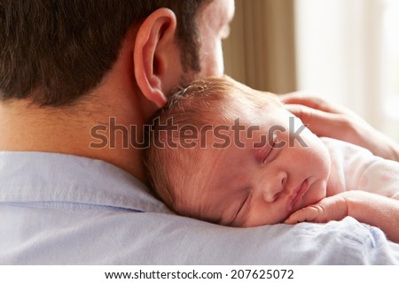 Father At Home With Sleeping Newborn Baby Daughter - stock photo