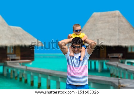 Father carrying baby on shoulders, having fun on Maldives, walking on the bridge to water villas - stock photo