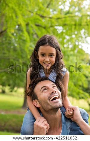 Father carrying daughter on his shoulders and smiling outdoors - stock photo