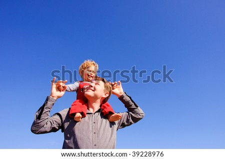 Father carrying his son piggyback - stock photo