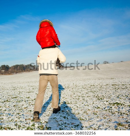 Father carrying his son piggyback. view from the back. Baby Boy Son On The Shoulders Of Dad in the winter. happy family with the sky on background - stock photo