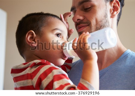 Father Carrying Young Son As He Drinks Milk From Bottle - stock photo