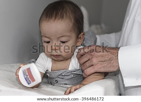 Father changing and dressing up 9 months baby in the baby room - stock photo
