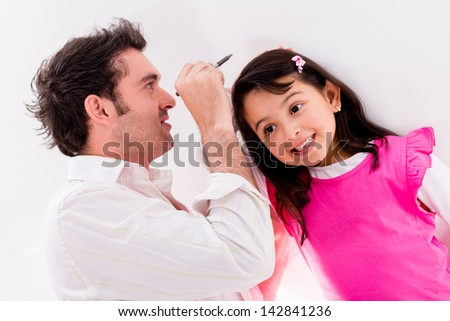 Father checking daughters height against the wall - stock photo