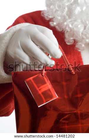 Father Christmas holding shopping gift bag - stock photo