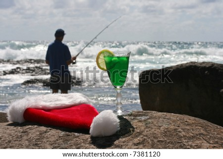 Father Christmas on Boxing Day relaxing fishing after the busiest nigh of the year, showing his hat, clothes and a festive cocktail resting on the rocks and the ocean in the background - stock photo