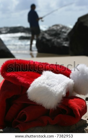 Father Christmas on Boxing Day relaxing fishing after the busiest night of the year, showing his hat and clothes  resting on the beach and the ocean in the background - stock photo