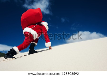 Father Christmas on the beach climbing up a sand dune with copyspace - stock photo