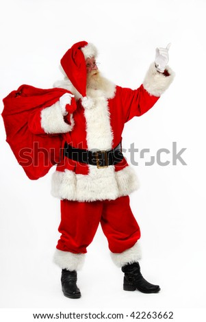 father christmas pointing with his finger as he carries his sack - stock photo