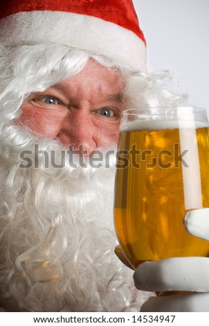 Father Christmas Santa looks at a lovely glass of beer - stock photo