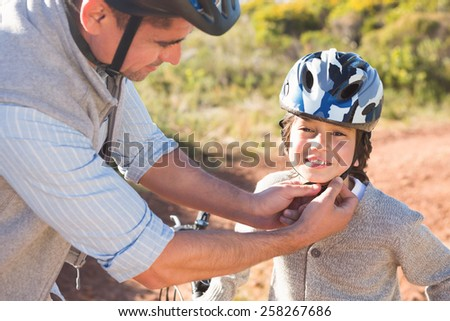 Father clipping on sons helmet on a sunny day - stock photo