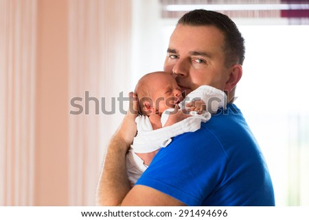Father cuddling crying baby girl on arm - stock photo