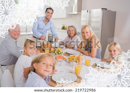 Father cutting turkey and looking at camera against snowflake frame - stock photo