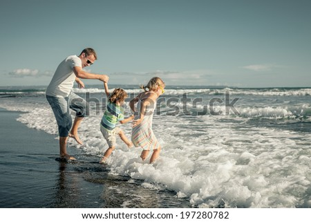 father, daughter and son playing on the beach at the day time - stock photo