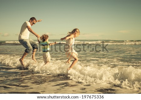 father, daughter and son playing on the beach at the day time