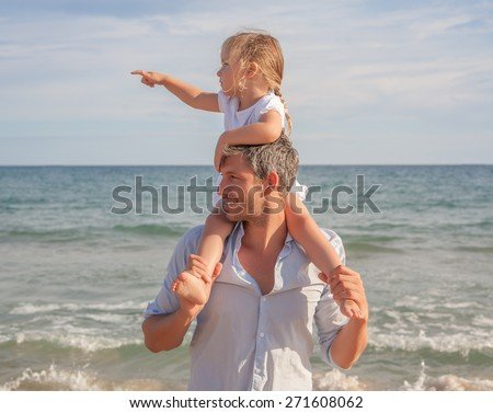 father daughter showing beach coast