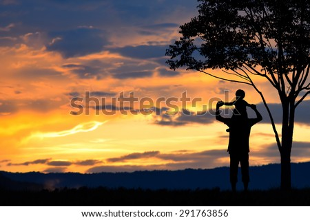 Father day ,father and son silhouettes play at sunset mountain blurred background - stock photo