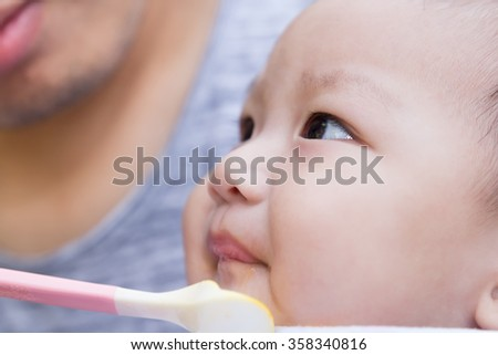Father feeding baby food to cute newborn baby  - stock photo