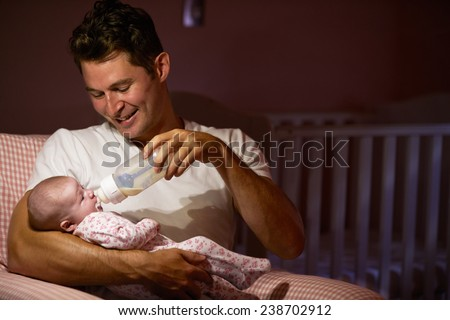 Father Feeding Baby With Bottle In Nursery - stock photo