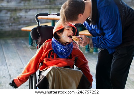 Father feeding disabled son a hamburger in wheelchair. Child has cerebral palsy - stock photo