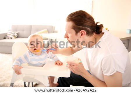 Father feeding his baby son