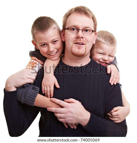Father gets hugged by his two smiling sons - stock photo