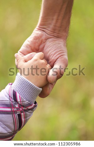 father gives the child's hand - stock photo