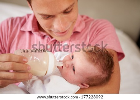Father Giving Baby Daughter Bottle Of Milk - stock photo