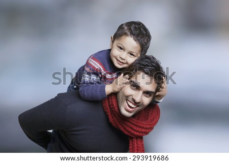 Father giving boy piggy back ride outdoors - stock photo