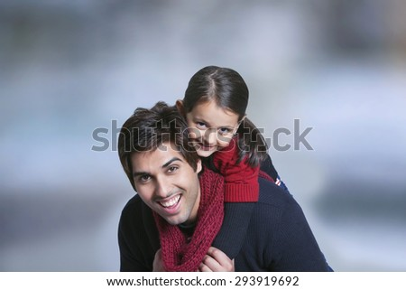 Father giving girl piggy back ride outdoors - stock photo