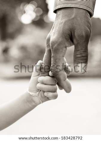 Father giving hand to a child - stock photo
