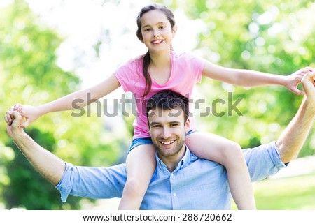 Father giving his daughter a piggyback - stock photo
